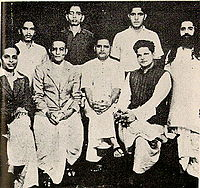 A group photo of people accused in the Mahatma Gandhi murder case. Standing: Shankar Kistaiya, Gopal Godse, Madanlal Pahwa, Digambar Badge (Approver). Sitting: Narayan Apte, Vinayak D. Savarkar, Nathuram Godse, Vishnu Karkare